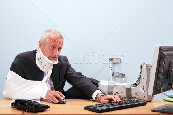 Injured businessman working at his desk Stock photo © RTimages
