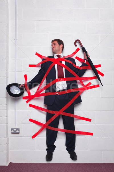 Businessman stuck to wall with red tape Stock photo © RTimages