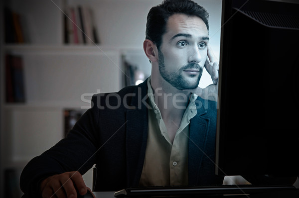 Suprised Man Looking At A Computer Monitor Stock photo © ruigsantos