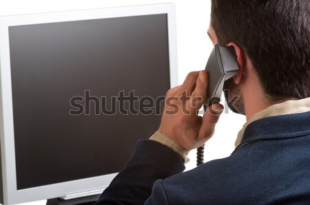 Casual Businessman Talking over the Phone and Looking at a Compu Stock photo © ruigsantos