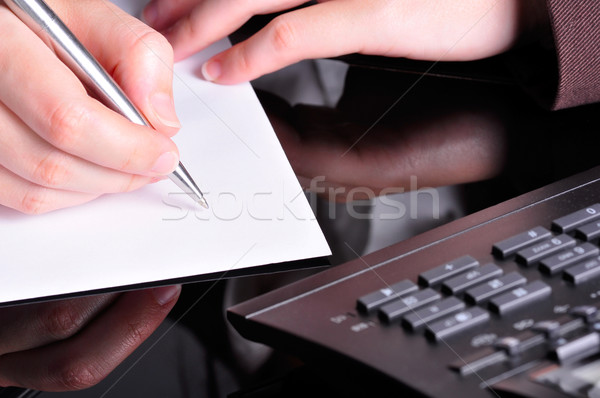 A hand, holding a pen, is ready to write on a document with a telephone next to it. Stock photo © ruigsantos