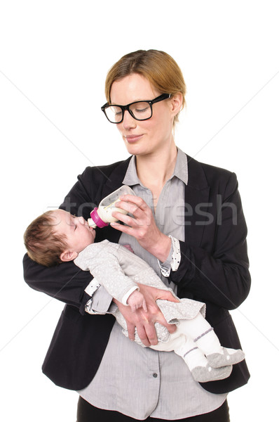 Businesswoman gives a baby the bottle Stock photo © runzelkorn
