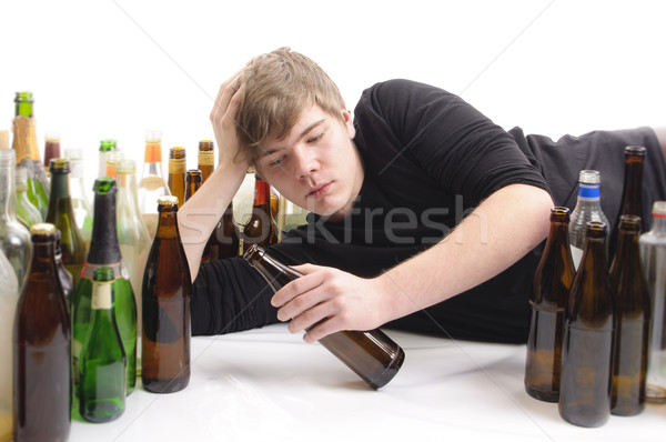 Young man alcohol abuse, holding beer bottle Stock photo © runzelkorn