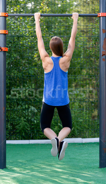 Young athletic girl hanging on the bar. Stock photo © RuslanOmega