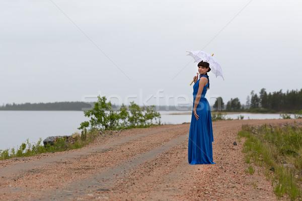 Gyönyörű lány kék ruha esernyő vidéki út víz Stock fotó © RuslanOmega