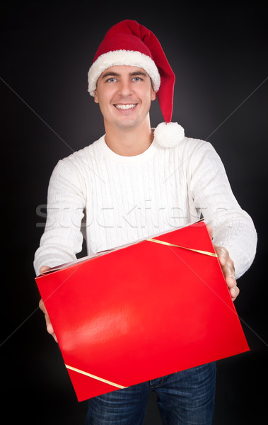 261d97a553bac Smiling man in Santa hat gives a red box in the studio stock photo ...