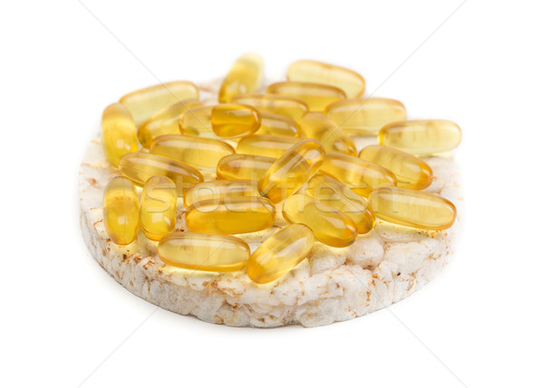 Stock photo: Sandwich from a round loaf and omega 3 pills.