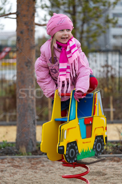 Stock photo: Little girl on the carousel in the autumn