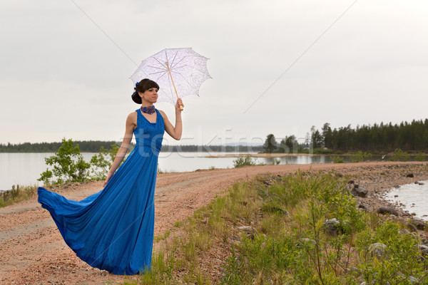 A girl tries to keep a umbrella which pulls out a wind. Stock photo © RuslanOmega