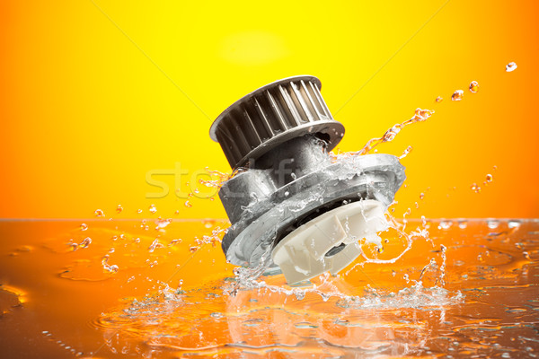Auto parts, engine cooling pump in water splash on orange backgr Stock photo © RuslanOmega
