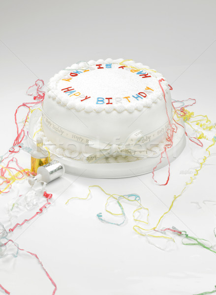 Birthday cake and streamers Stock photo © russwitherington