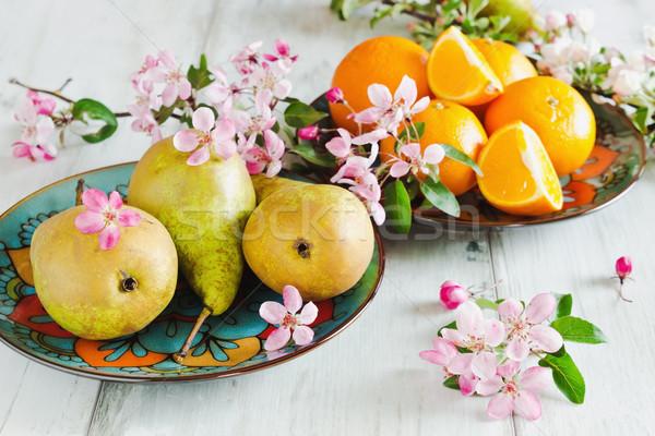Körték narancsok tányérok asztal virágok háttér Stock fotó © saharosa