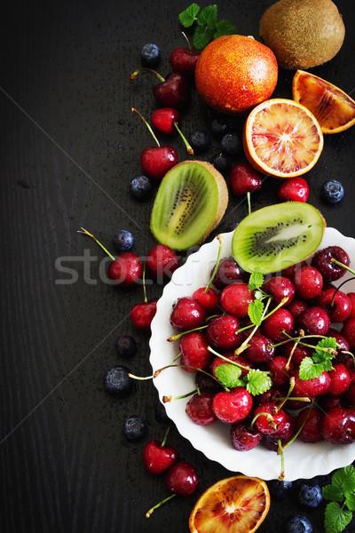 Különböző gyümölcsök bogyók érett fehér tányér Stock fotó © saharosa