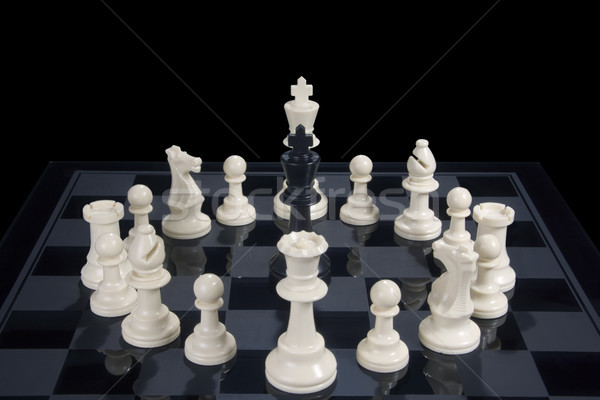 Chess Black King Circled by White Pieces Stock photo © saje