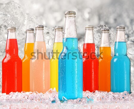 Bottles of multi-color drinks with ice on white Stock photo © Sandralise