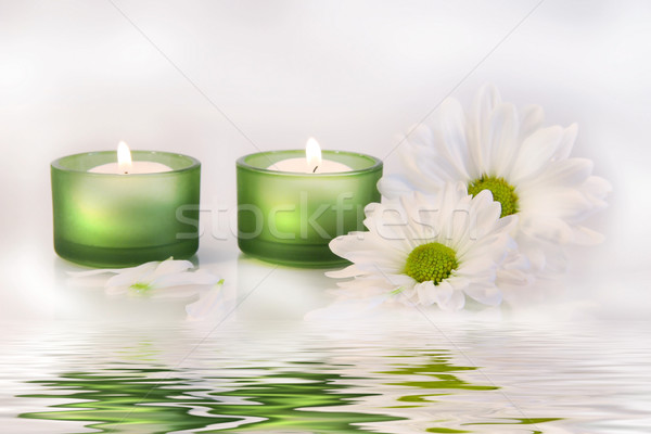Green candles and daisies near water reflection Stock photo © Sandralise