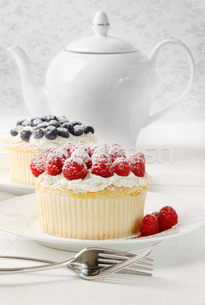 Cupcakes with raspberries and cream on table Stock photo © Sandralise
