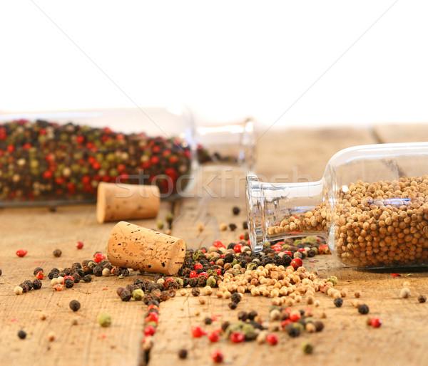 Peppercorns in glass bottles on wood table Stock photo © Sandralise