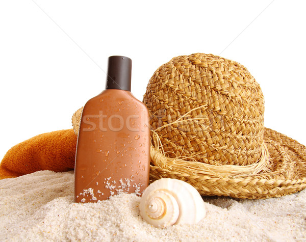 Straw hat with towel and suntan lotion on white Stock photo © Sandralise