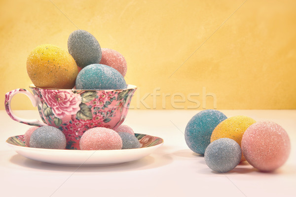 Brightly colored eggs in tea cup Stock photo © Sandralise