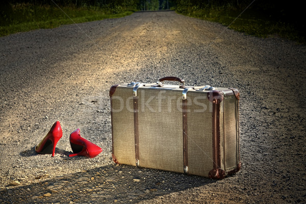 Old suitcase with red shoes left on road Stock photo © Sandralise