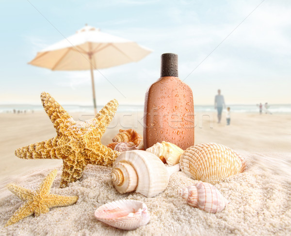Stock photo: Suntan lotion and seashells on the beach
