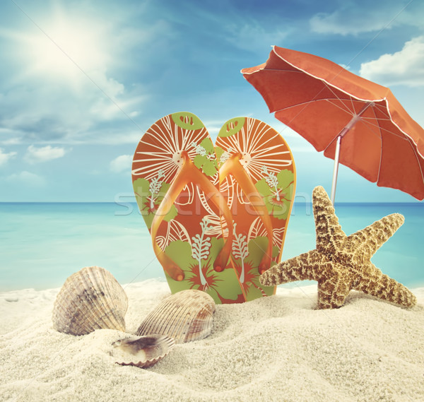 Sandals and starfish with beach umbrella at the ocean Stock photo © Sandralise
