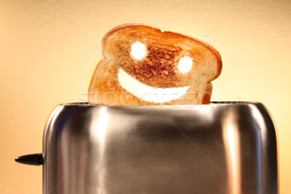 Toast with smiley face in toaster  on counter Stock photo © Sandralise