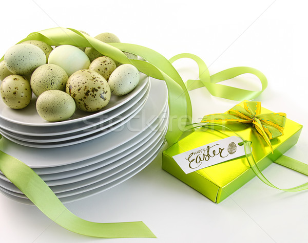 Easter eggs on plates with ribbons and gift Stock photo © Sandralise