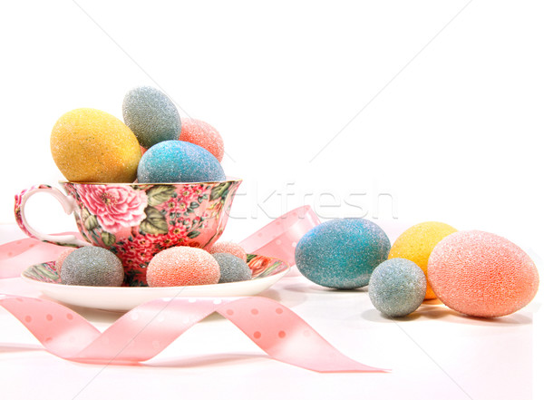 Brightly colored eggs in tea cup on white Stock photo © Sandralise