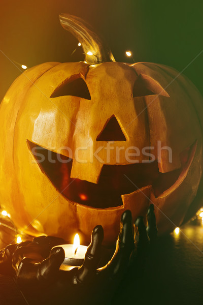 Close up of pumpkin with candle in black hand                    Stock photo © Sandralise