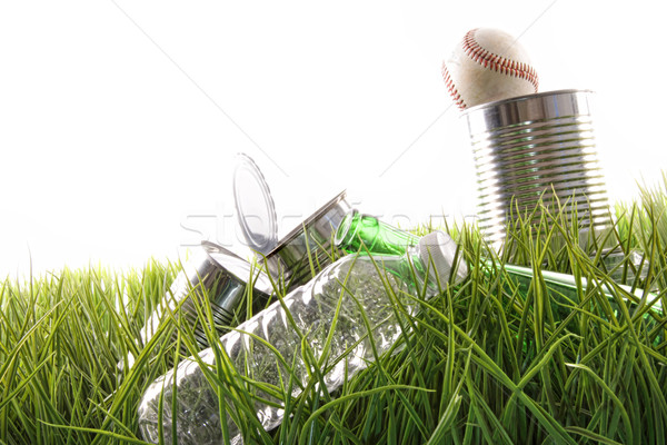 Empty food cans, bottles and baseball in grass Stock photo © Sandralise