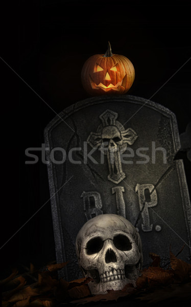 Spooky tombstone with skull and pumpkin on black Stock photo © Sandralise