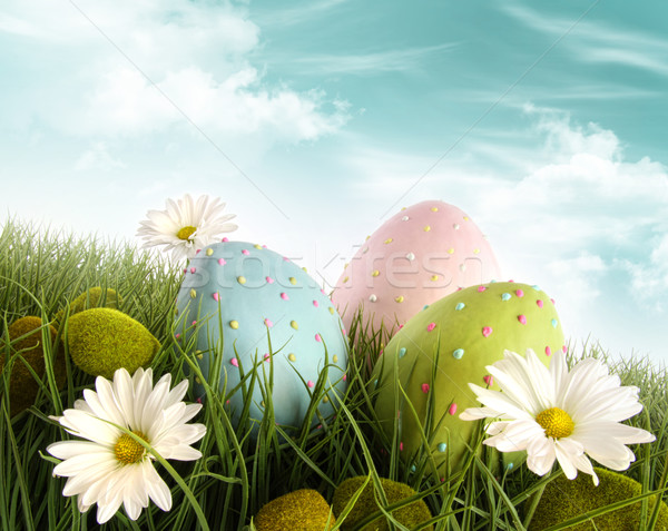 Three decorated easter eggs in the grass with daisies Stock photo © Sandralise