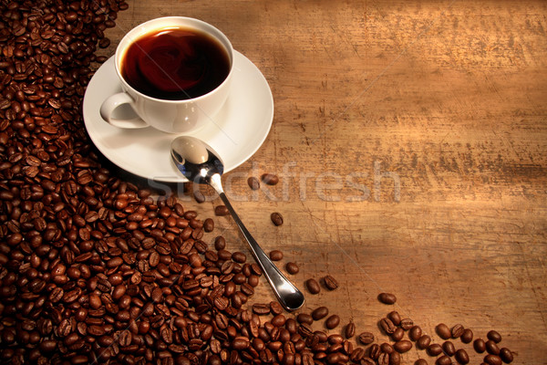 Stock photo: White coffee cup with beans on rustic  table
