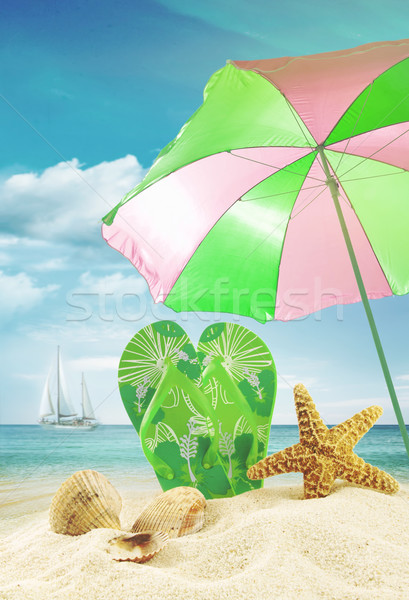 Sandals and seashells with umbrella at the ocean Stock photo © Sandralise