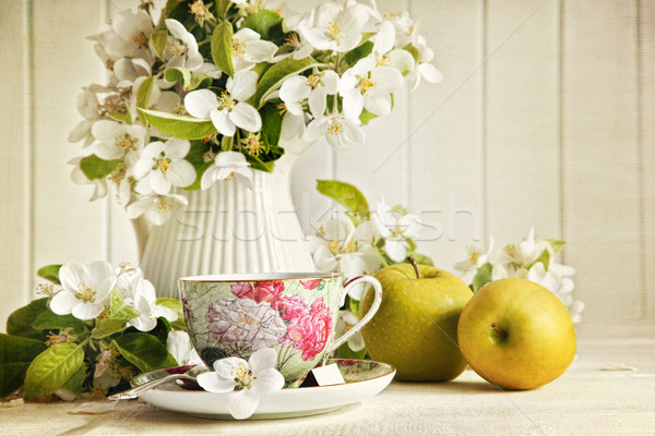 Tea cup with flower blossoms and green apples Stock photo © Sandralise