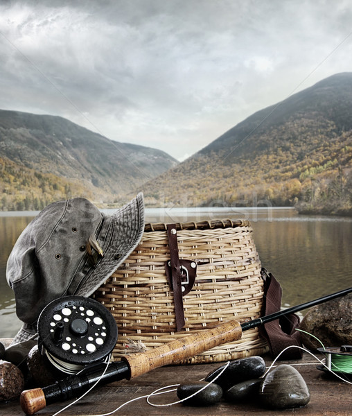 Stock photo: Fly rod with creel and equipment on wood