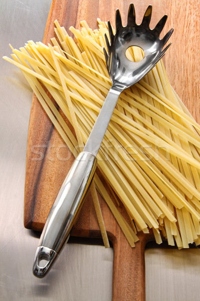Stock photo: Fettuccine on wooden cutting board
