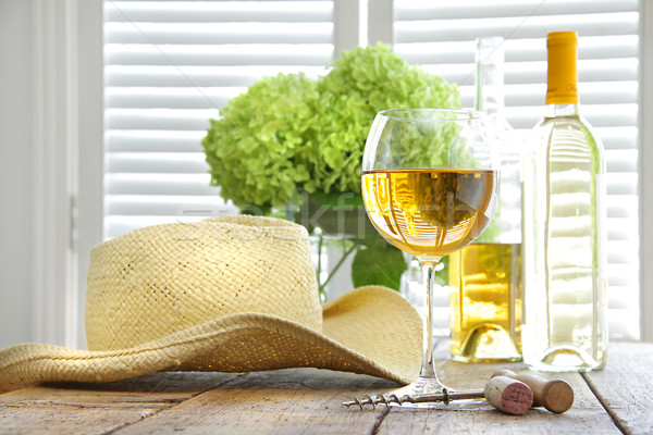 Stock photo: Glass of wine with straw hat on table