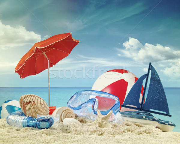 Beach toys on sandy beach with blue sea in background Stock photo © Sandralise