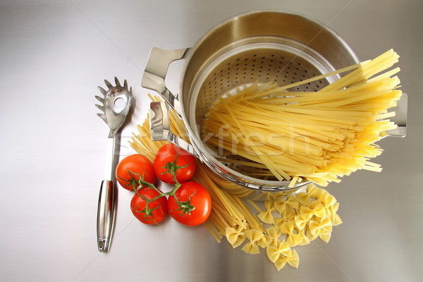 Overhead shot of pasta, tomatoes and pot on stainless steel Stock photo © Sandralise