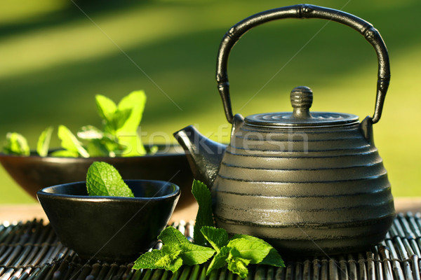 Black asian teapot with mint tea Stock photo © Sandralise