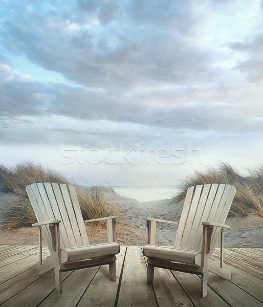 Convés cadeiras areia oceano pôr do sol Foto stock © Sandralise