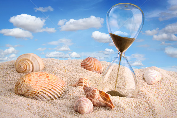 Hourglass in the sand with blue sky Stock photo © Sandralise