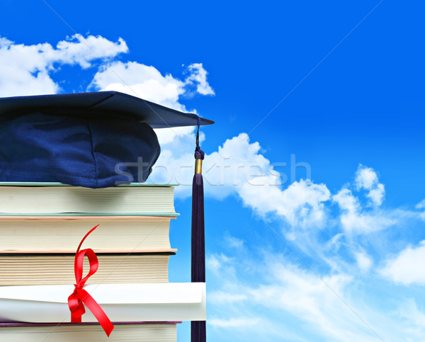 Stock photo: Stack of books with diploma against blue sky