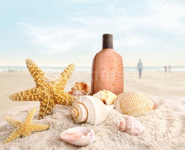 Suntan lotion and seashells on the beach Stock photo © Sandralise