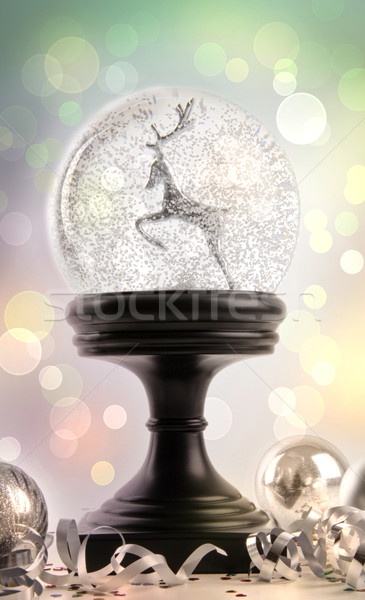 Snowglobe with ornaments against colored background Stock photo © Sandralise