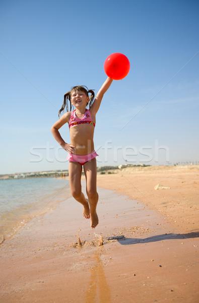 Menina saltando balão praia céu água Foto stock © sapegina