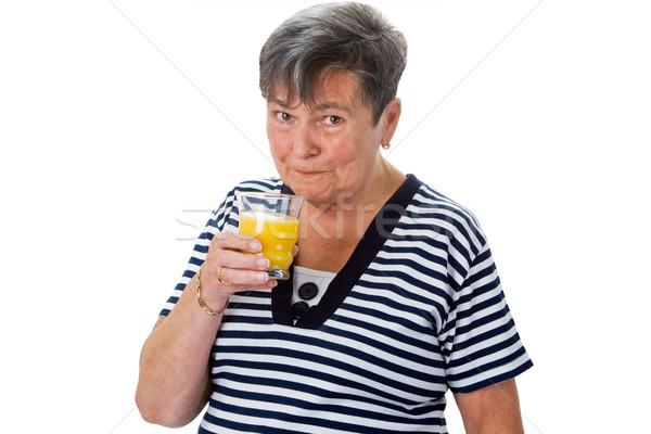 Elderly woman drinking orange juice Stock photo © Saphira